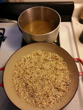 Heating the broth and frying the arborio rice.